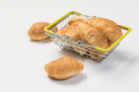 Small croissants in a metal basket with yellow handles on a white table. Breakfast dish.