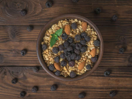 Black raspberries scattered on the table and a bowl of granola. The dish is rich in fiber.