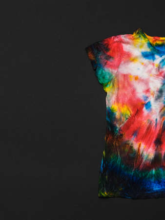 Half t-shirt in tie dye style on a black background. White clothes painted by hand. Flat lay. Place for text.