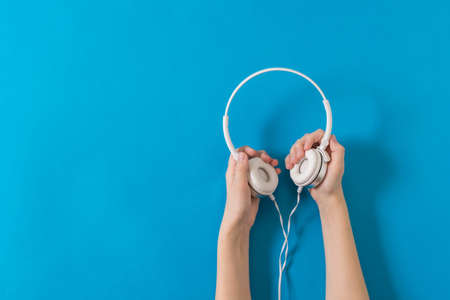 Two hands holding white headphones on a blue background. Mobile audio playback equipment. Stock Photo