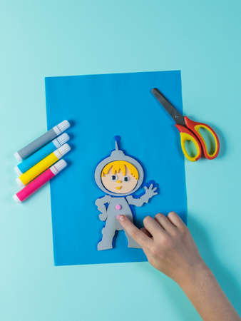 Scissors, markers and paper crafts on a blue background. The creativity of paper. Stock Photo