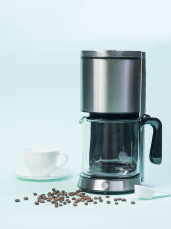 White Cup, coffee maker and coffee maker on blue background. The concept of a classic Breakfast. Stock Photo