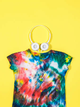 White headphones and a tie dye t-shirt on a yellow background. White clothes painted by hand. Flat lay.