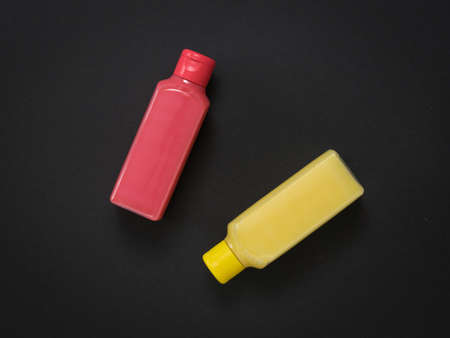 Two plastic bottles with soap solution on a black background. Plastic utensils for the storage of liquids. Stock Photo