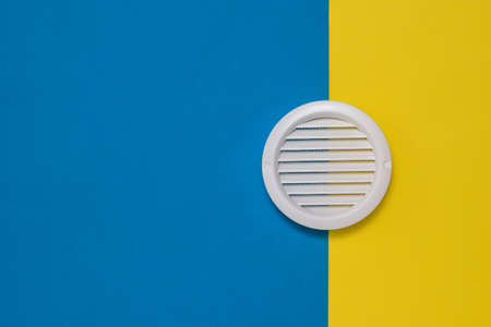 Round white ventilation grate on a two-color background. Devices for fresh air supply.