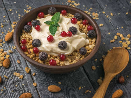 Black raspberries and red currants in a bowl with granola and yogurt. The view from the top.