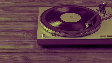 A tinted image of a vinyl record player with the disc mounted on a wooden table. Music on vinyl discs. 写真素材
