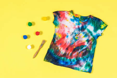 Tie dye t-shirt with scattered colors on a yellow background. White clothes painted by hand. Flat lay.