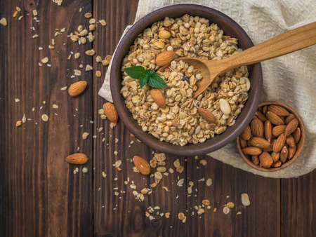 Granola and almonds in a clay bowl on a wooden table. The dish is rich in fiber.