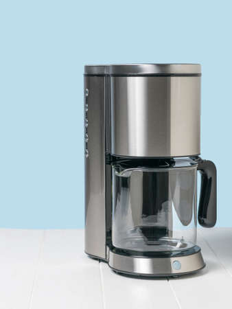 Metal drip coffee maker on a white table. The concept of a classic Breakfast.