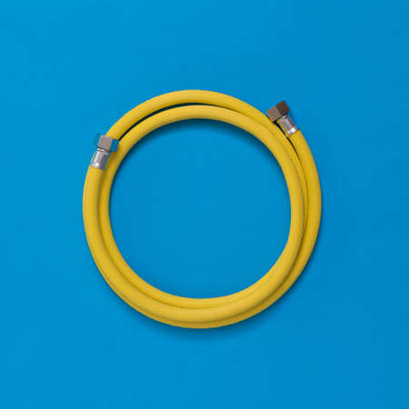 Yellow gas hose coiled on a blue background. Organization of natural gas supply. Reklamní fotografie