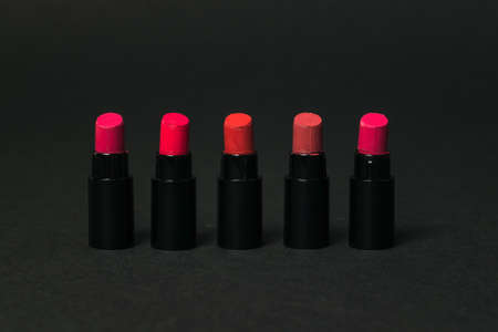 Five samples of red lipstick on a black background. Cosmetics for lips.
