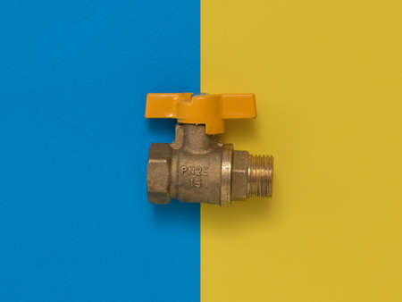 Yellow gas tap on a yellow and blue background. Organization of natural gas supply.
