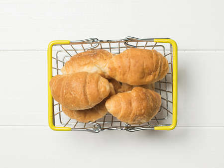 A few croissants in an iron basket on a white table. The view from the top. Breakfast dish.