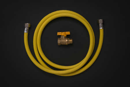 A coiled gas hose and a gas tap on a black background. Organization of natural gas supply.
