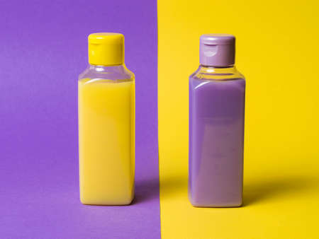 Two plastic bottles with a yellow and lilac product on a two-color background. Cosmetic product in a plastic bottle. Reklamní fotografie