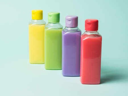 Colored plastic bottles with liquids on a light background. Cosmetic product in a plastic bottle.