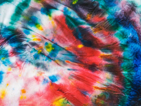 Multi-colored tie dye background made of crumpled fabric. White clothes painted by hand.