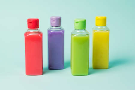 Plastic bottles of four colors on a blue background. Cosmetic product in a plastic bottle.