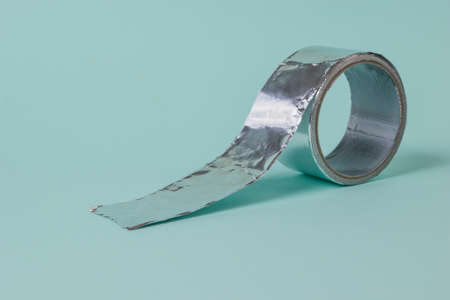 Metal adhesive tape on a light blue background. Tape for packaging and sealing.