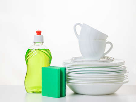 A set of clean dishes, gel and a set of foam sponges on a white table. The concept of cleaning and maintaining cleanliness.