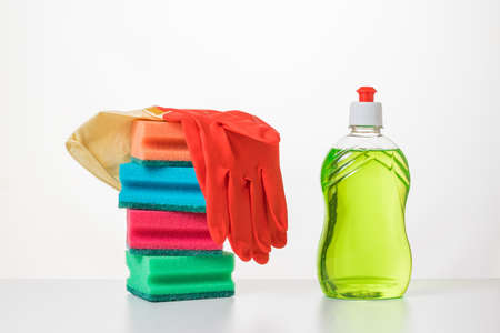 A set of foam sponges, dish washing gel and gloves on a white table. The concept of cleaning and maintaining cleanliness.