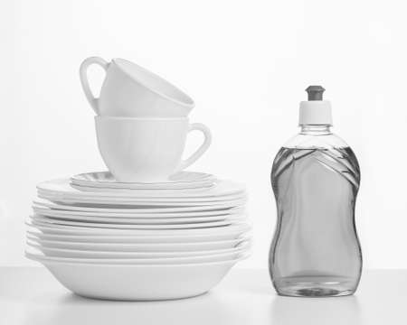 Black and white image of a gel bottle and a set of dishes on a white table. The concept of cleaning and maintaining cleanliness. 写真素材
