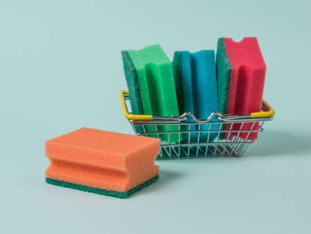 Several foam sponges in a metal basket on a blue background. The concept of cleaning and maintaining cleanliness.