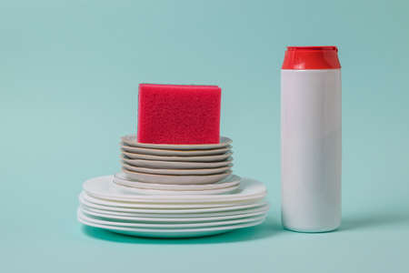 Cleaning powder, red foam sponge and a set of clean dishes on a blue background. The concept of cleaning and maintaining cleanliness.