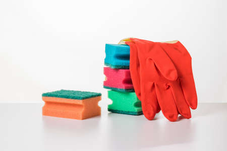 A set of foam sponges and rubber gloves on a white table. The concept of cleaning and maintaining cleanliness.