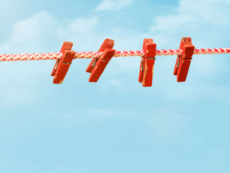 Four red clothespins on a clothesline against the sky. Device for drying clothes. 写真素材