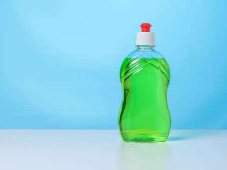 A bottle of green cleaning gel on a white table on a blue background. The concept of cleaning and maintaining cleanliness. 写真素材