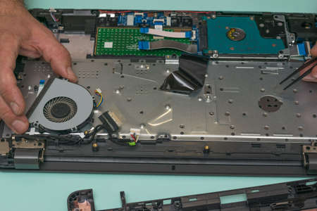 A man changes the cooling fan in a laptop. Repair and restore laptop performance. 写真素材