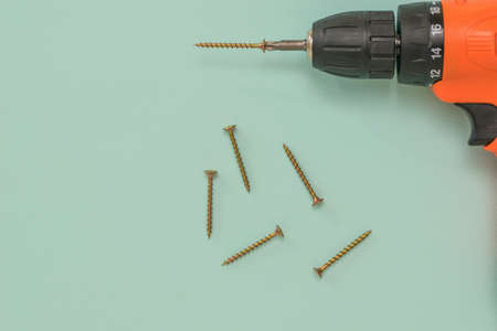 Six yellow metal screws and a cordless drill on a blue background. A tool with a battery.