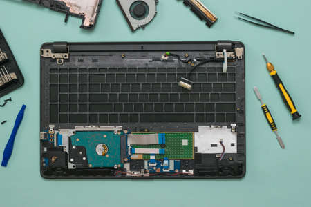 Disassembled laptop, screwdrivers and tweezers on a blue background. Repair and restore laptop performance.