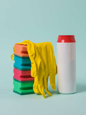 A stack of foam sponges, yellow gloves, and cleaning powder on a blue background. Cleaning the house and office.