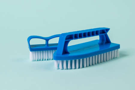 Two blue cleaning brushes on a blue background. The concept of cleanliness in the house.