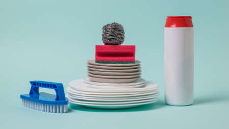 Dish brushes, cleaning powder and a set of white dishes on a blue background. The concept of cleaning and maintaining cleanliness.