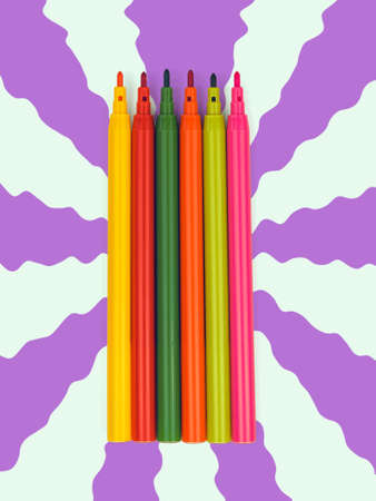 A set of markers in warm colors on an abstract background. Universal markers for school, office, and Hobbies.