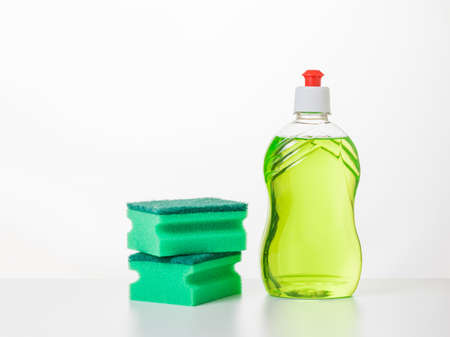 Two green foam sponges and dish washing gel on a white table. The concept of cleaning and maintaining cleanliness.