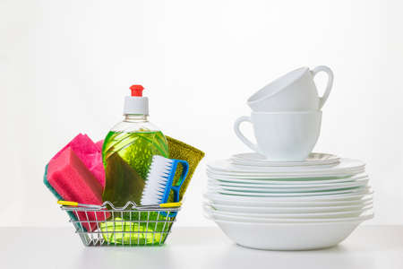 Dishwashers in a metal basket and clean dishes on a white table. The concept of cleaning and maintaining cleanliness. 写真素材