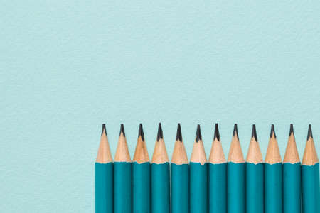 Sharpened graphite pencils on a blue background. Paper and office supplies.