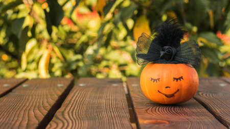 Pumpkin with a smiling face in a black hat on a wooden table. Autumn pumpkin harvest. 写真素材