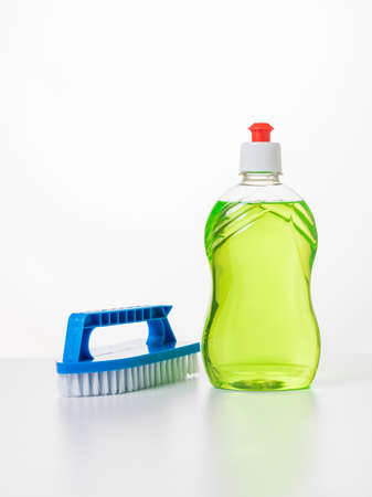 Green detergent and a blue brush on a white table. The concept of cleaning and maintaining cleanliness.