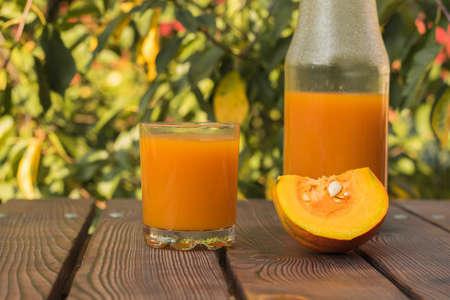 A piece of pumpkin, a glass and a bottle of pumpkin juice. Autumn pumpkin harvest. 写真素材