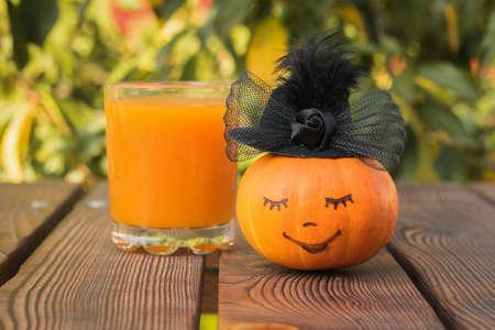 Pumpkin in a woman's black hat on a wooden table. Autumn pumpkin harvest.