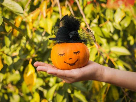 A child's hand holds a pumpkin in a woman's hat. Autumn pumpkin harvest.