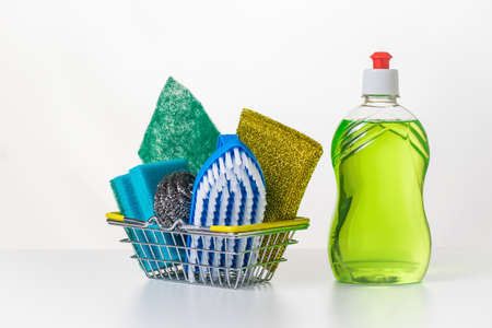 Green gel and a set of rags and brushes on a white table. The concept of cleaning and maintaining cleanliness. 写真素材
