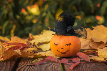 Pumpkin with a painted face in a black hat on a wooden table with leaves. Autumn pumpkin harvest.