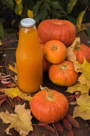 Ripe pumpkin fruits, autumn leaves and a bottle of pumpkin juice on a wooden table. Autumn pumpkin harvest.